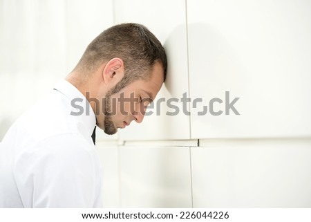 Unemployed man, stressed for there is no work. Beats head against wall. - stock photo