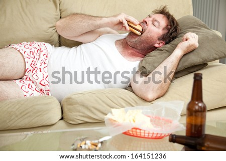 Unemployed middle aged man at home on the couch in his underwear, eating a hamburger,  with a marijuana joint in the ashtray and beer bottles lying around. - stock photo