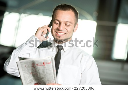 Unemployed, smiling man is looking for a job in the newspaper and calling. - stock photo