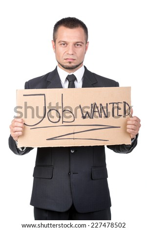 Unemployed unrecognizable businessman is showing a message in a cardboard that he needs a job. - stock photo