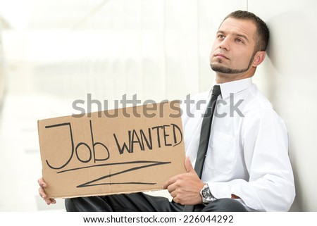 Unemployed young man is sitting with a sign Job wanted. - stock photo