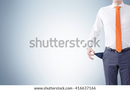 Unemployment concept with businessman showing empty pocket on light grey background. Mock up - stock photo