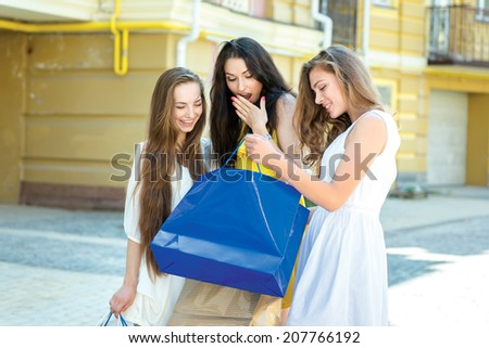 Unexpected purchase in the shop. Three attractive young girl holding shopping bags while considering buying packages and sharing their impressions - stock photo