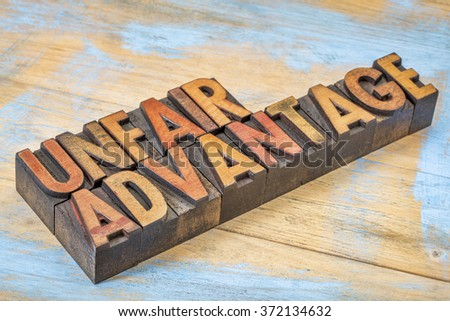 unfair advantage - word abstract n vintage letterpress wood type blocks stained by color inks - stock photo