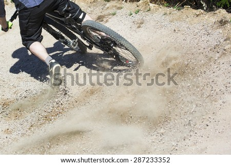 Unfiltered version of mountain bike rider drifting through a gravity slope of an artificial downhill track. Gravel sprays upwards. - stock photo