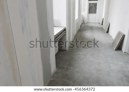 Unfinished apartment interior with door and gray concrete floor - stock photo