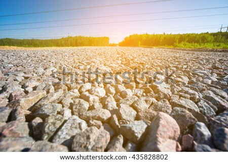 Unfinished asphalt country road in pine forest. Under construction. Break stone paving - stock photo