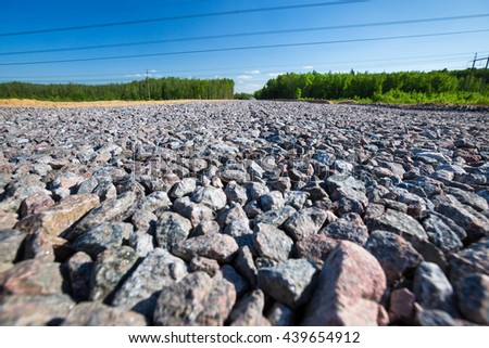 Unfinished asphalt country road in pine forest. Under construction. Breakstone paving - stock photo