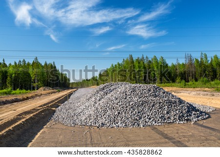 Unfinished asphalt country road in the forest. Pile of break stones on construction site - stock photo