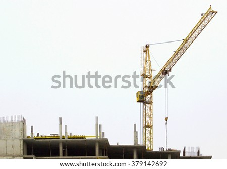 Unfinished building construction site with crane - stock photo