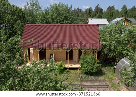 Unfinished wooden house in the garden. - stock photo