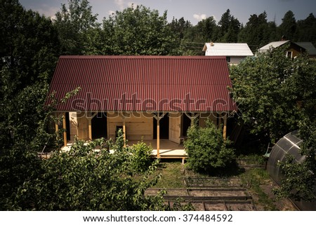 Unfinished wooden house in the garden. Toned. - stock photo