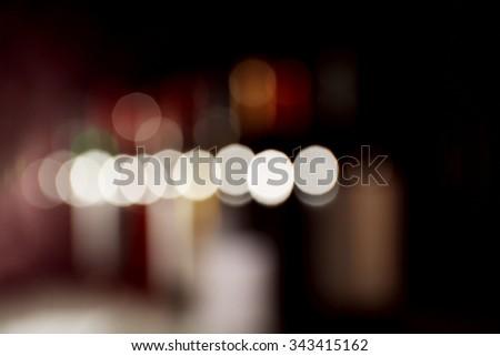 unfocused wine bottles on black background - stock photo