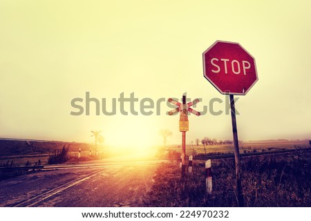 Unguarded railway crossing in a rural landscape - stock photo