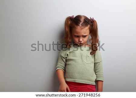 Unhappy abandoned kid girl looking down on blue background with empty copy space - stock photo