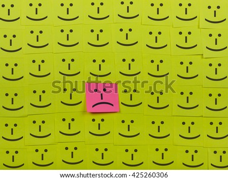 Unhappy and happy concept. Background of green sticky notes. Unhappy sticky note is among happy sticky notes. - stock photo