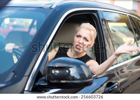 Unhappy and nervous young woman while driving in traffic jam - stock photo