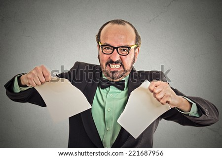 Unhappy angry businessman tearing a document to pieces - stock photo