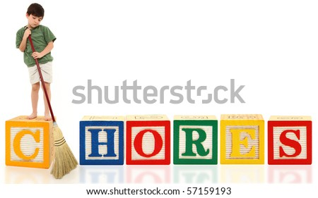Unhappy attractive 7 year old french american boy doing chores with broom over white background.  Alphabet blocks spell Chores. - stock photo