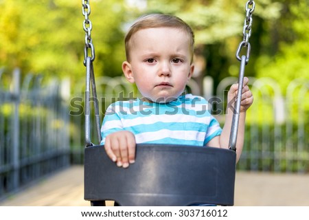 Unhappy baby boy looking at camera on the swing in the park - stock photo