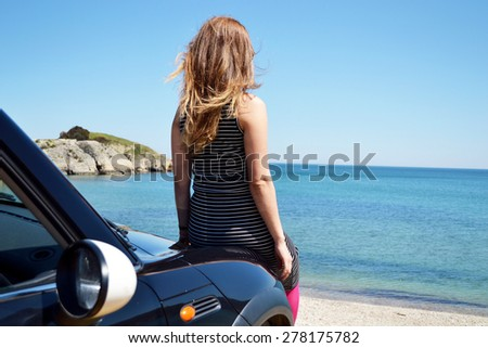 unhappy beautiful blond young woman driving a sports car - stock photo