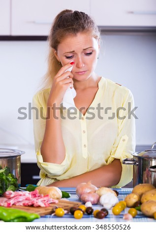 Unhappy blonde woman looking at dinner ingredients with sad face