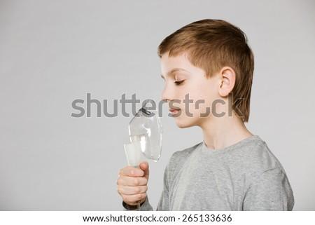 Unhappy boy breathing through inhalator mask on grey background - stock photo