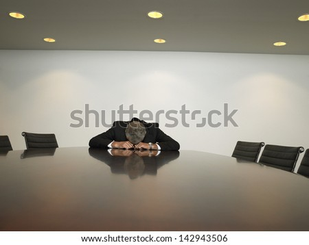 Unhappy businessman resting his head on table in conference room - stock photo