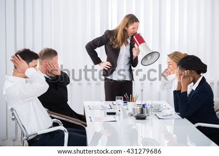 Unhappy Businesswoman Shouting Through Megaphone On Businesspeople In Office - stock photo