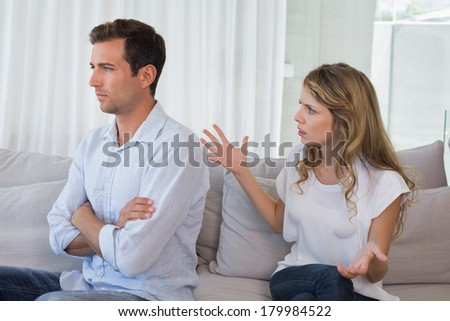 Unhappy couple having an argument in living room at home - stock photo
