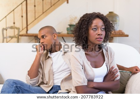 Unhappy couple not speaking to each other at home in the living room
