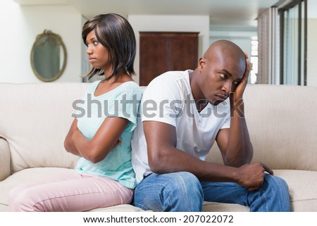 Unhappy couple not talking after argument on sofa at home in the living room - stock photo