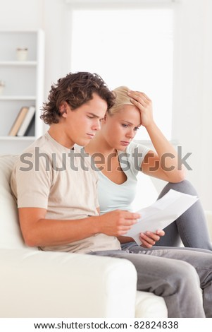 Unhappy couple reading letters in the living room