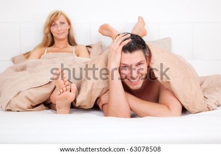 Unhappy couple sitting angry in bed - stock photo