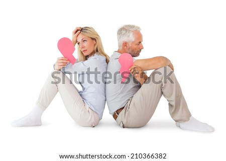 Unhappy couple sitting holding two halves of broken heart on white background - stock photo