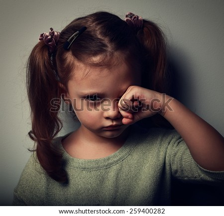 Unhappy crying kid girl in darkness. Closeup vintage portrait - stock photo