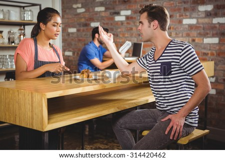 Unhappy customer complaining about the croissant in a cafe - stock photo