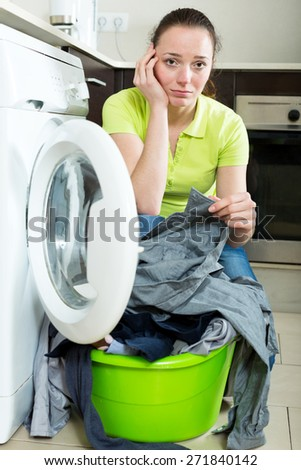 Unhappy girl with dirty clothes near washing machine - stock photo