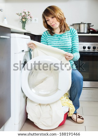 Unhappy  housewife with  clothes near washing machine