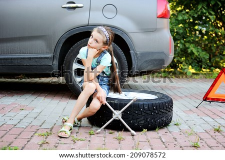 Unhappy kid girl sitting on the wheel and waiting her father to change broken wheel during the family trip - stock photo