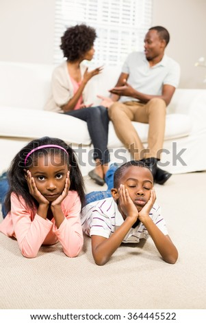 Unhappy kids sitting on the floor beside arguing parents