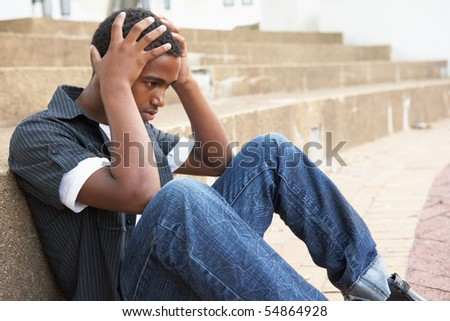 Unhappy Male Teenage Student Sitting Outside On College Steps - stock photo