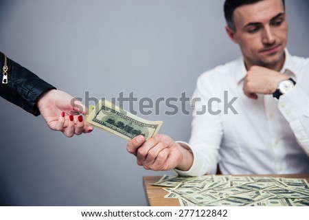 Unhappy man giving money to woman over gray background - stock photo