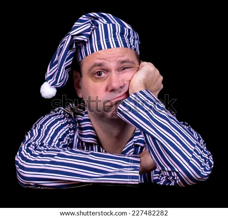 unhappy man in pajamas on a black background - stock photo