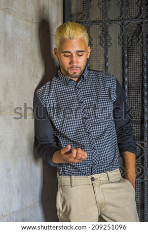 Unhappy Man. Wearing a black patterned shirt, yellow pants, a young guy with beard, yellow hair is leaning against the wall outside a metal gate, looking down on his fingers, sad, thinking. - stock photo