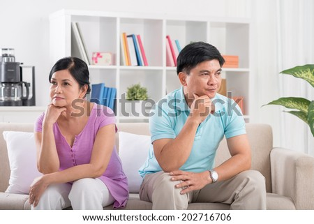 Unhappy married couple sitting on the sofa after having a quarrel - stock photo