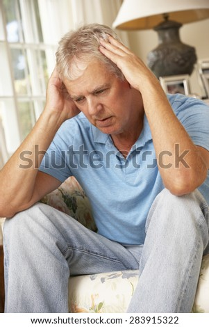 Unhappy Mature Man Sitting On Sofa At Home - stock photo