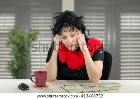 Unhappy middle-aged woman is sitting at white desk. The sad woman wears black dress and red scarf. There are maroon mug, keyboard on desk and unfocused shutters as background. Horizontal indoors shot. - stock photo