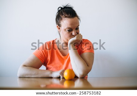 Unhappy overweight looking at orange. Diet concept. - stock photo
