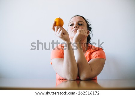 Unhappy overweight woman looking at orange. Diet concept. - stock photo